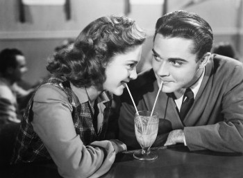 Vintage b/w photo of man and woman sharing a milkshake, while woman wonders if man just likes her for her large-cap stocks