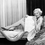 Black and white retro photo of flirtatious woman looking a viewer with large book