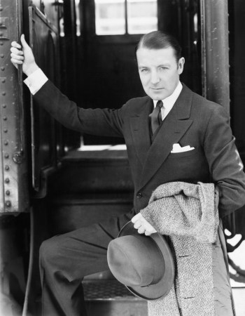 Black and white retro photo of wealthy looking man boarding a train