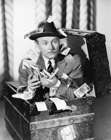 Black and white retro photo of man sitting in trunk with money prepared to pay high fees for equity indexed annuities