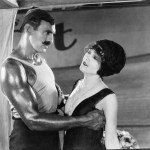 Body builder seducing woman to get her to buy an equity indexed annuity.
