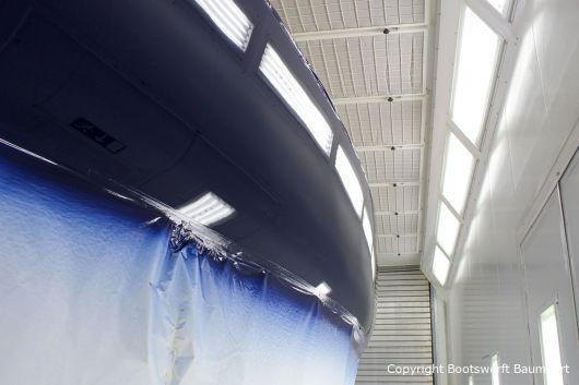 Erste Lackschicht in dunkelblau auf der Comfortina 38 Segelyacht. Backbordseite in der Lackierkabine der Bootswerft Baumgart in Dortmund