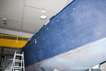 Vorbereitung zur Lackierung des Zierstreifens an der Steuerbordseite in der Werfthalle der Bootswerft Baumgart in Dortmund