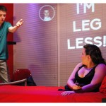 A woman sits on a bed looking at a man who is standing by her bed talking with one arm in the air. The phrase 'I'm Leg less' is projected on the back wall.