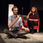 A man lays down on a grey shag rug. He is talking and gesticulating with his hands. A woman in a red armchair with a lamp beside it sits nearby.