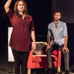 The woman is standing on the grey rug. She appears to be signing while the man sits on the arm of the red armchair and watches with admiration.