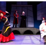 An actor sits at the front of the stage writing. A woman to his right is wearing a black dress that has a large red skirt and a large red feathered hat. stands with her arms up.