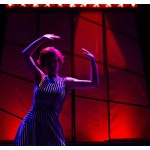 The stage is lit a dim red. An actress in a black and white striped dress stands with her arms in the air.
