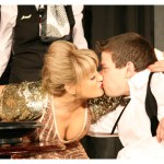 A woman in a sparkly dress and a man in a tuxedo kiss.