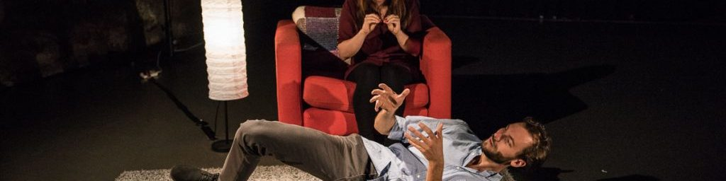 A man lays on the floor talking and gesticulating with his hands. A woman in a red armchair behind him watches.