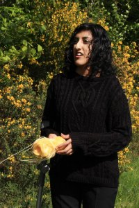 A photo of Aminder Virdee. She is wearing a black jumper and has long, wavy black hair.