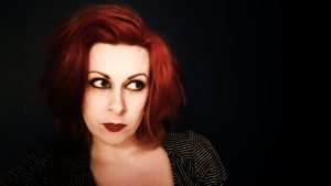 A photo of Jen McGregor. She is wearing red lipstick and has chin length red hair.