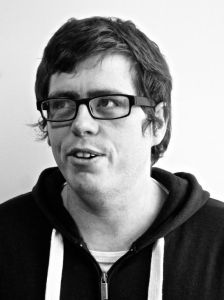 A black and white photo of Stuart Pyper. He has short brown hair and thick rectangular glasses