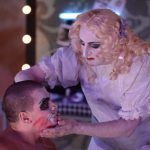 A drag queen with long blonde hair wearing a white dress does the makeup of another actor.