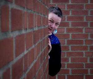 A photo of Caroline Parker. She has short dark hair and is peering out playfully from behind a red brick wall.