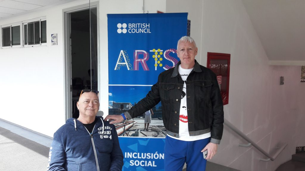 A photograph of Garry Robson and Kinny Gardner. They are in front of a banner that says 'British Council: Arts'
