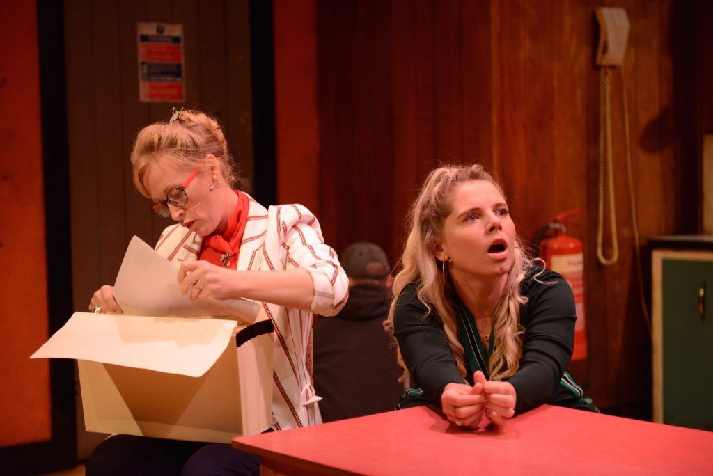 2 actors are on stage. One of them is looking through a box of things, and the other is looking at something outside of the photo with a shocked expression on her face