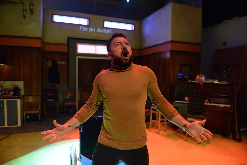 An actors is singing at the front of the stage his mouth and his arms are open wide.
