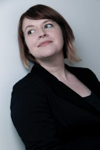 A photo of Emily Reutlinger. She has brown hair that is tied back and is wearing a black blazer.