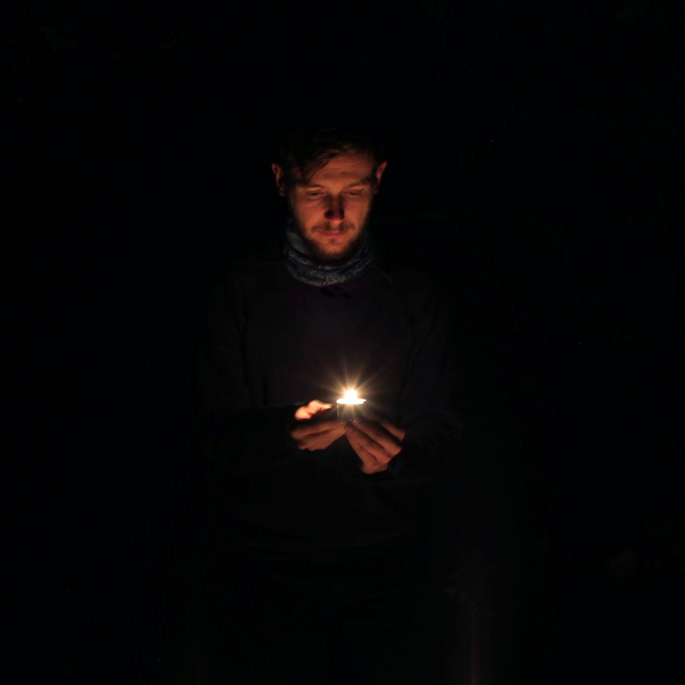 Thom Scullion looks down at a candle burning in his hands. He is a white man in his 30s. His face is bathed in an orange glow while around him is darkness.