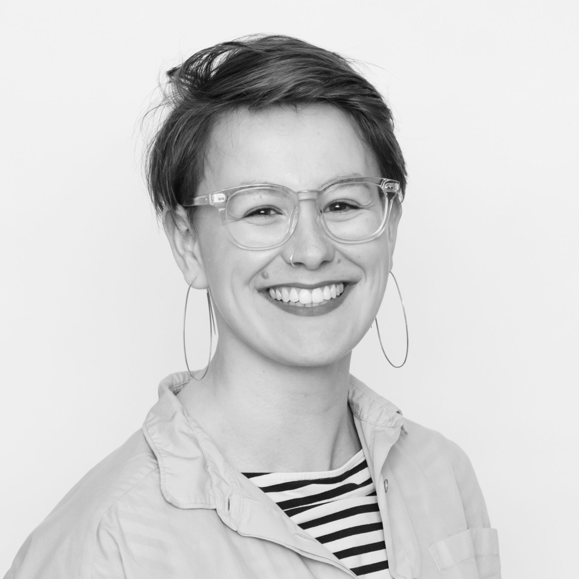 Black and white headshot of Any Watson: a white woman in her 30s with short hair. she has a shit over a stripy t-shirt, big hoop earrings, glasses and a big smile