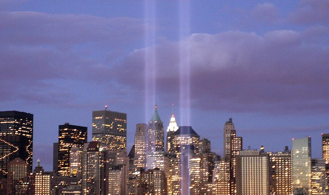 Image of tribute in lights to Word Trade Center towers and NYC skyline at dusk.