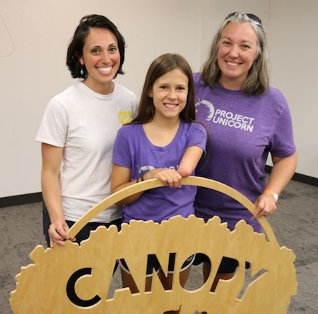 """Three people smile while holding a sign that says """"Canopy."""""""