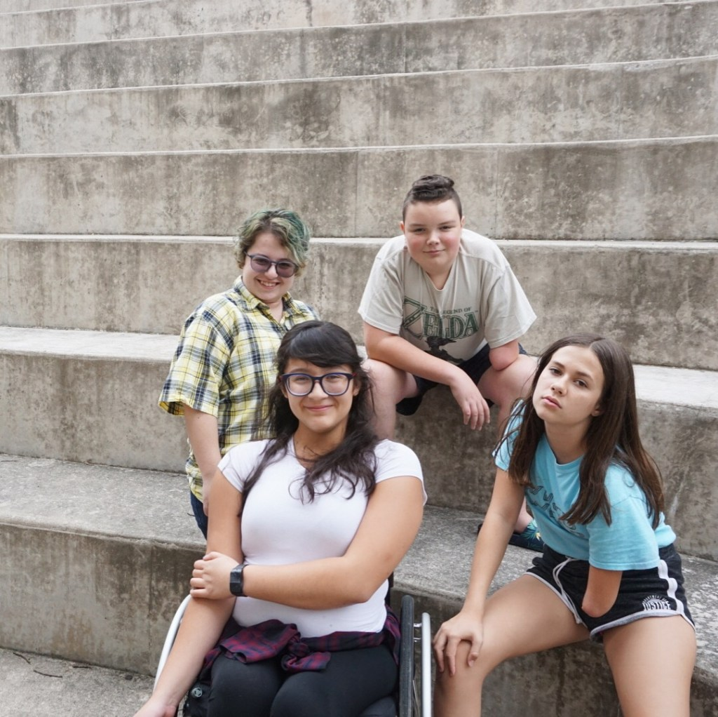 Four young people sit near or on concrete steps.