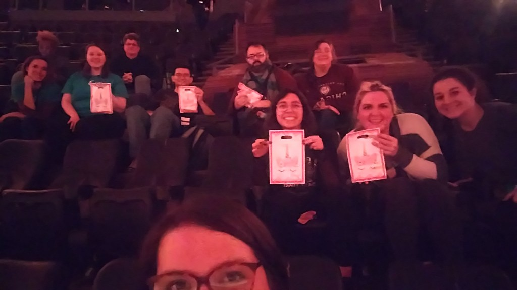 A group of people sitting in a theater smile and hold up bags with unicorns on the front.