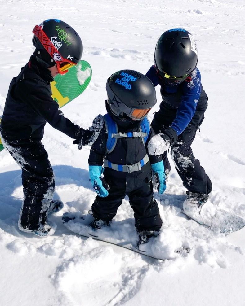 Teaching baby to snowboard