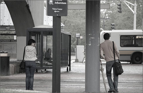 image of a woman and a man, both waiting at a stop