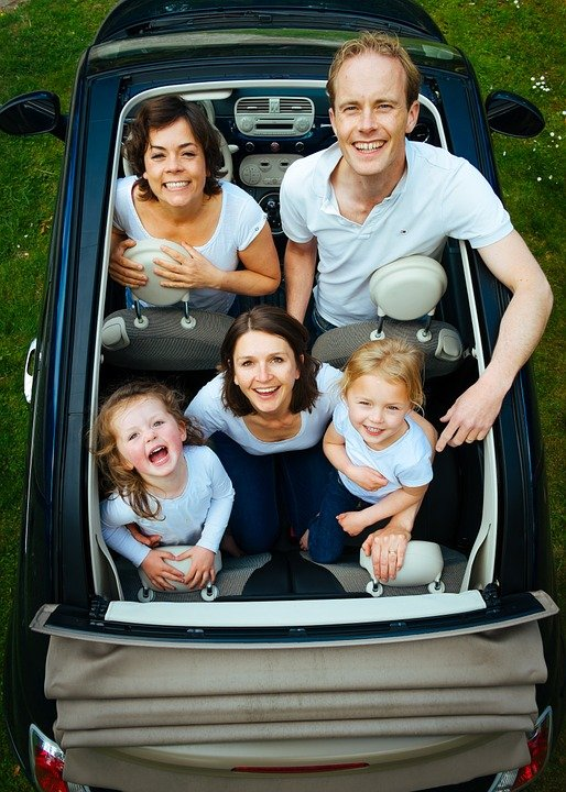 Kids and parents in mini convertible car shot from above