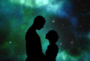 Lovers in silhouette in front of starry sky scene