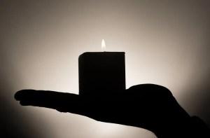 Lit candle balanced on palm