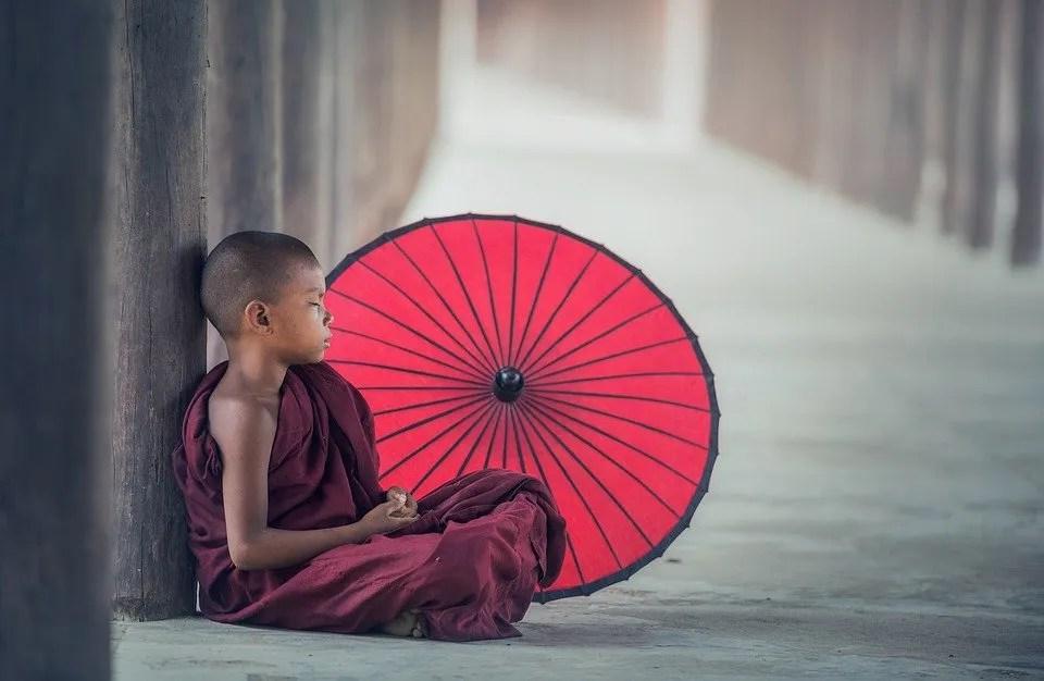 Meditating Boy with Red Umbrella
