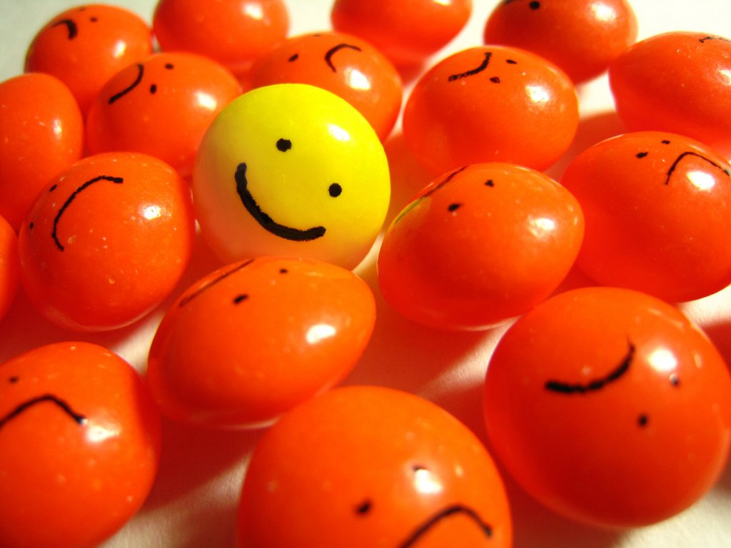 field of frowny balls surrounding smiley ball