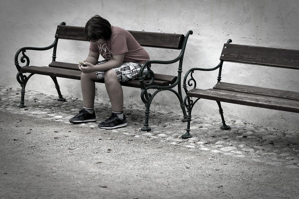 Sad Teen sitting alone on bench