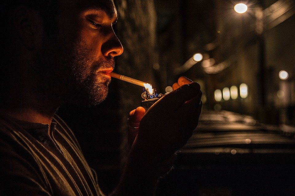 Man lighting cigarette at night