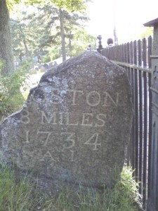 Milestone indicating 8 miles to Boston, 1734, bearing the initials AI which stands for Alexander Ireland, a surveyor. Removed to a place inside the fence of the First Parish Cemetery, Cambridge, in 1892, it is located near the grave of the man whose initials it bears.