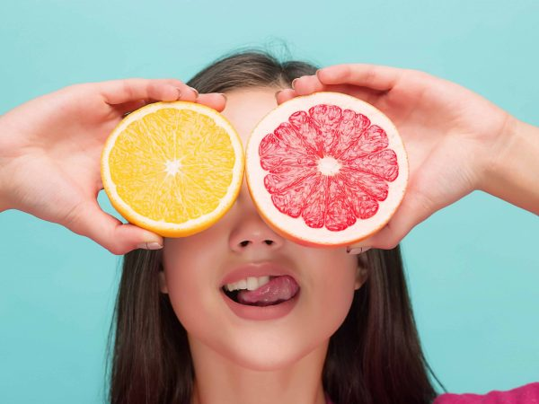 Beautiful woman's face with delicious orange and grapefruit at studio
