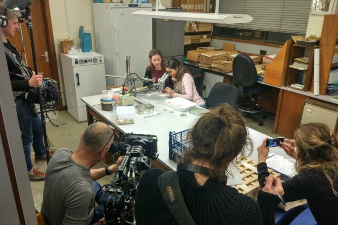 Many people in a tiny room while filming in the Herbarium