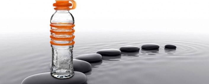 A orange glass water bottle is seen perched on rocks in water