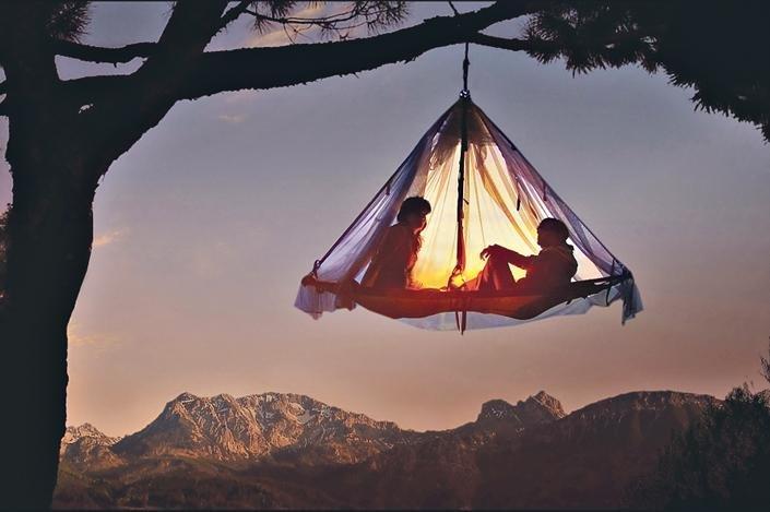 egy emberpár egy fán függő sátorban