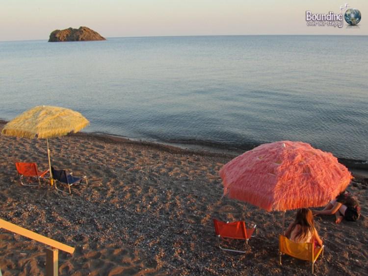Beach umbrellas line the beach at Eresos in Lesbos, Greece
