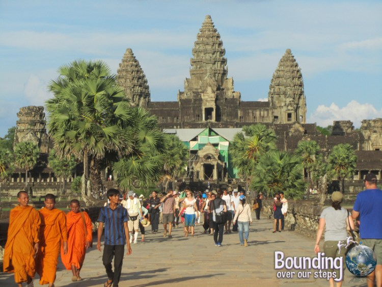 Orange-clothed monks walking away from the main temple of Angkor Wat