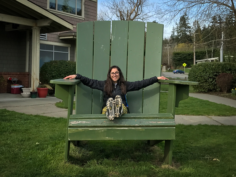 Angelina Boulicault sitting in a giant green chair on Bainbridge Island, Washington. Boundless Journey