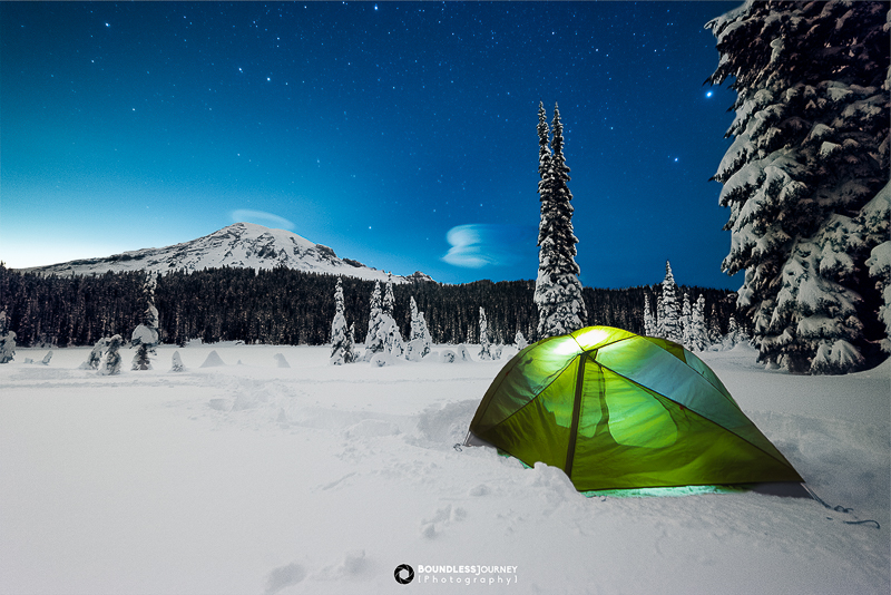 A glowing tent tent with Mt. Rainier in the background. Winter camping tips.
