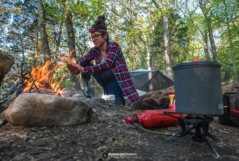Angelina at the camp fire with an MSR Whisperlite Universal camp stove cooking dinner. Boundless Journey Photography.Outdoors gifts.