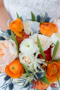 Orange and white ranunculi with garden roses for a bridal bouquet.