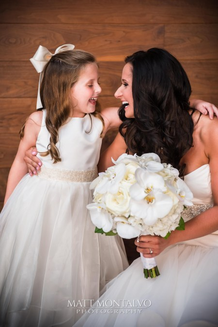 Bride with all white classic bridal bouquet including garden roses and phaelnopsis orchid blooms.